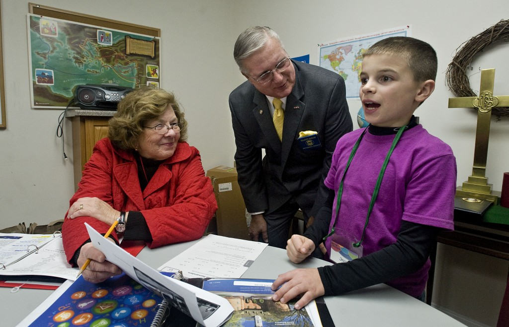 Retired teacher Margaret Gochenour, left, a Hamburg Ruritan member, works with  Jesse Lemon,9, of Edinburg while Elliott Hogge, center, president of Ruritan National, looks over his  shoulder during the after school tutoring and enrichment program at Zion Lutheran Church in Hamburg. Rich Cooley/Daily