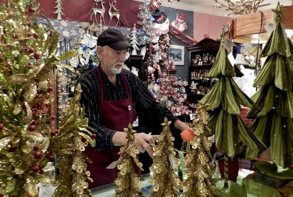 Tony Suarez, owner of the Christmas Gallery, straightens his wares on a cold, rainy December afternoon. Suarez has been in business since 1977.  Henry Culvyhouse/Daily