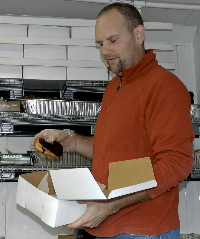 Frank Emswiler fills a box of a donuts at the Strite's truck in New Market. Photo by Henry Culvyhouse