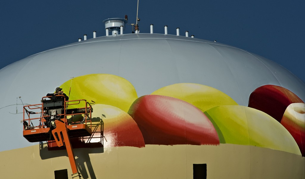Eric Henn chats on his cell phone while taking a break from painting this basket of apples on top of Mount Jackson's water tank near Interstate 81.  Henn is expected to finish before Christmas. Rich Cooley/Daily