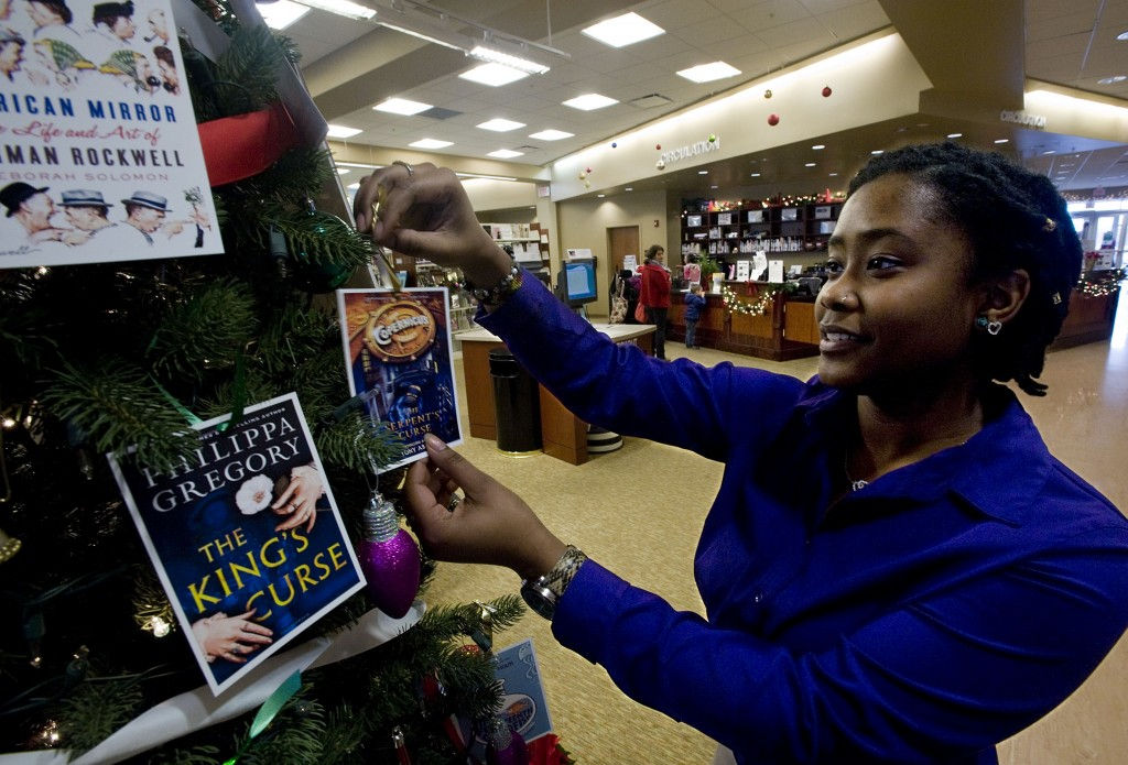 Shikira Barrett, reference assistant at Samuels Public Library in Front Royal, puts a book card on a tree inside the library on Tuesday. The library is conducting a fundraiser - patrons can buy cards representing their favorite books and can create a memoir honoring or remembering a person that would be printed inside the library book.  Some local libraries are experiencing budget cuts and are taking action to compensate for the revenue loss.  Rich Cooley/Daily