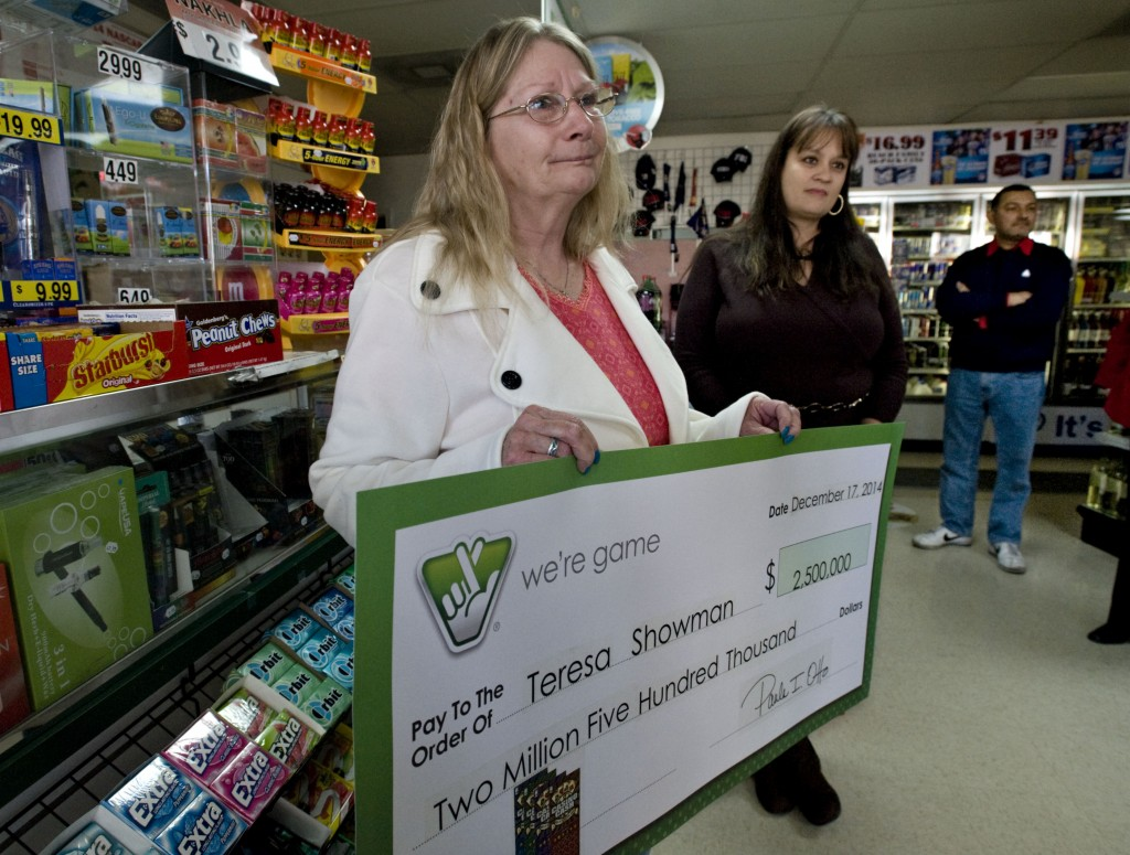 Teresa Showman, 59, of Maurertown, holds the replica of her $2.5 million dollar check inside the Express Mart at 203 South Main St. in Woodstock. Showman, a cross country truck driver,  won the top prize in Virginia Lottery's Casino Cash Scratcher game. Showman's daughter, Nicole Shoemaker, is standing at right and the store owner, Syed Jafri, is at the far right. Rich Cooley/Daily