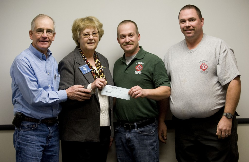 Mark Staff, center, president of the Shenandoah County Career Firefighters Association Local 7483, presents a check to Shirley Colvin, incoming zone governor for the Shenandoah County Ruritan Clubs, for $1,000 to be used for the nine countywide Ruritan Clubs Empty Stocking Fund. At left is Dennis Morris, incoming lieutenant governor for Shenandoah County, and at right is Michael Gochenour, treasurer for the County Career Firefighters Association. The county Ruritans have spent  $35,000 for county needy families and their fundraising efforts are continuing.   Daily Staff Photo