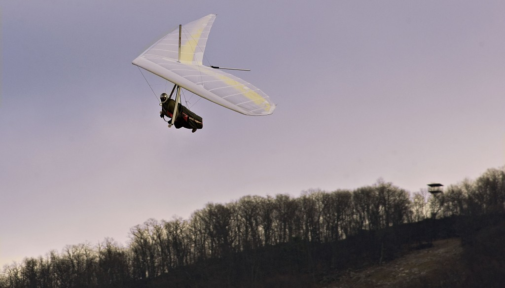 Larry Smith comes in for a landing in his hang glider off Tower Road east of Woodstock on a cold winter afternoon. Rich Cooley/Daily