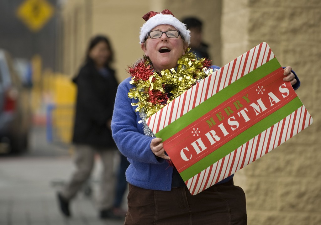 Rebecca Young, of Edinburg, is decked in the Christmas spirit as she sings outside the Walmart in Woodstock on Tuesday afternoon. Young is a teacher at Central HIgh School in Woodstock. Schools dismissed Tuesday afternoon for the Christmas holiday.  Rich Cooley/Daily