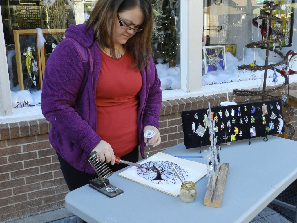 Erin Riley, owner of Old Town Stained Glass, solders a frame on a sun catcher outside her shop in Winchester on Friday. Riley said because the weather was nice, she decided to work outside, which increased interest from passing shoppers. Photo by Henry Culvyhouse