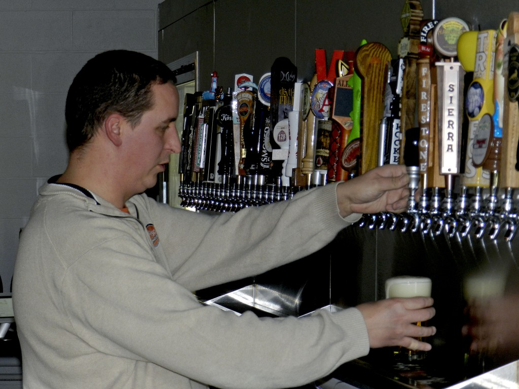 Jason Connolly, owner of The 50/50 Taphouse, pours a beer. The bar offers 50 craft beers on tap. Photo by Henry Culvyhouse