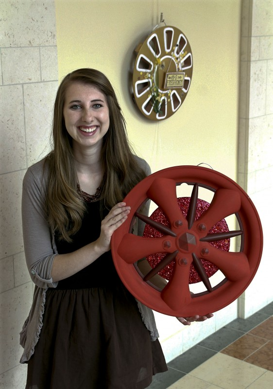 "Frederick County resident Hana Malone, 18, holds an example of her hubcap art at The Museum of the Shenandoah Valley in Winchester. The youngest artist ever to exhibit her work in the museum's Art in the Halls series, she has displayed her hubcap art in the show ""Second Time Around: The Hubcap as Art.""  Courtesy photo"