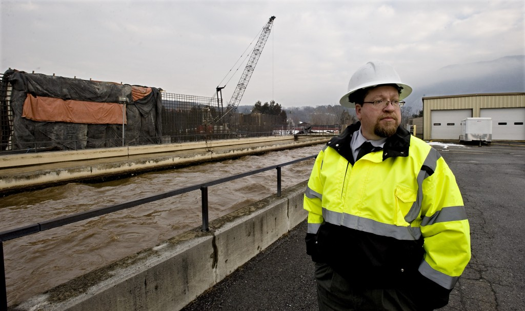 Jay McKinley, interim Strasburg town manager, stands outside the oxidation ditch at the town's wastewater sewer plant. New construction upgrades include a system being constructed that cleans the water by removing nitrogen and phosphorous.  Rich Cooley/Daily