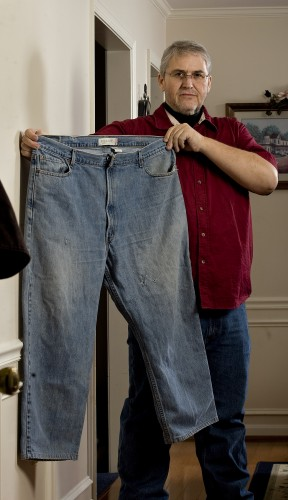 Tom Murden, 48, of Woodstock, holds a pair of50-inch waist jeans he wore before his surgery.  Murden is down to a 32-inch waist after losing 200 pounds. Rich Cooley/Daily