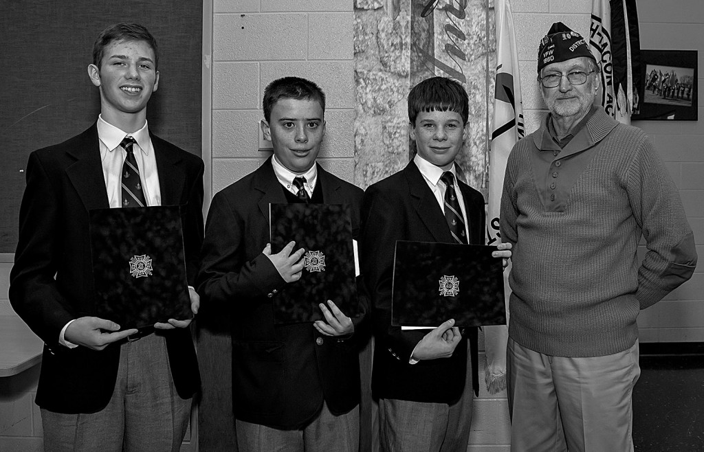 Griffin Loper, from left,  Jonathan Bunker and Jacob Gehly accept their awards from VFW Quarter Master/Adjutant Scott Simmons. The three Randolph-Macon Academy Middle School students took top honors in the awards contest sponsored by the Front Royal VFW Post 1860 and Ladies Auxiliary.  Courtesy photo