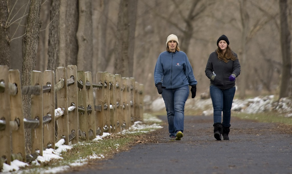 Paula Conroe, left, and her daughter Melissa Fisher, right, both of Front Royal, take a brisk walk along the Eastham Park Trail on a cold winter afternoon. Rich Cooley/Daily