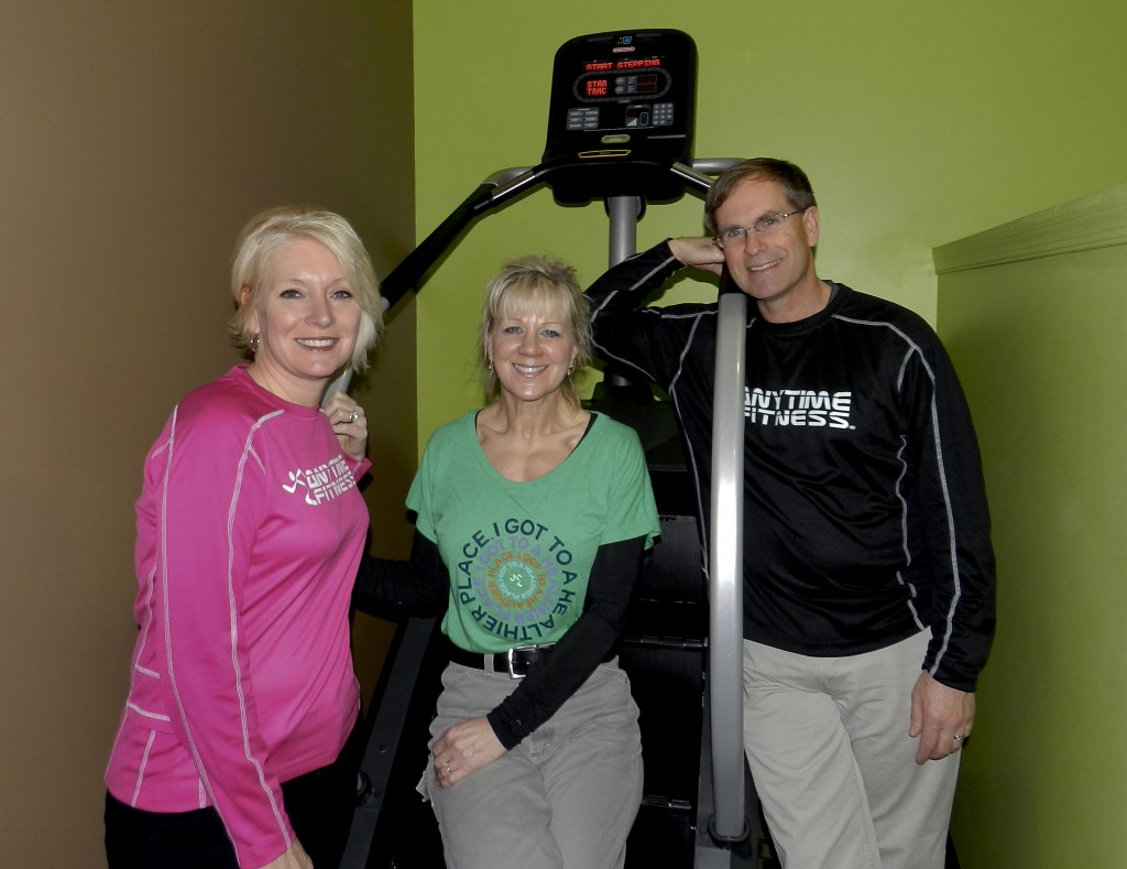 Anytime Fitness co-owner Alice Muellerweiss, from left, manager Debbie Simmons and co-owner Kevin Watson stand next to a stair stepper at the Strasburg business.  Muellerweiss and Watson bought Anytime Fitness in December. Henry Culvyhouse/Daily