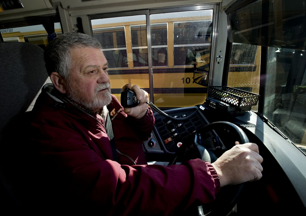 John Gangwer, a Shenandoah County School bus driver, holds a two-way radio microphone while parked outside Central High School in Woodstock on Monday. School officials say the  bus radios are outdated and need to be replaced with a new communications system. Rich Cooley/Daily