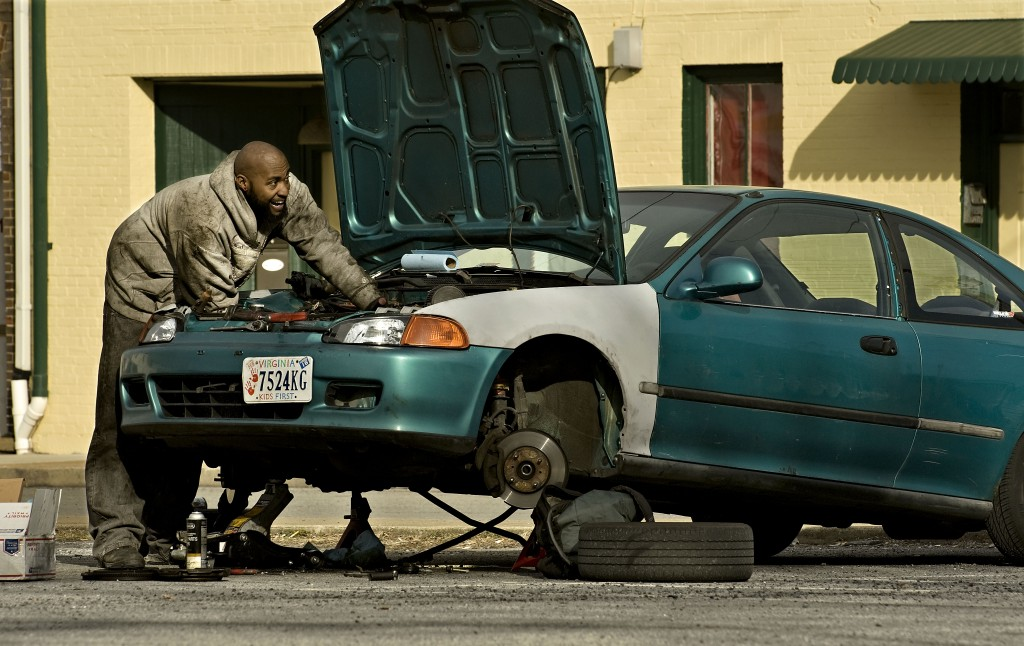 Tyrone Ambers  works on replacing the clutch in his car outside his apartment off Blue Ridge Avenue in Front Royal recently.   Rich Cooley/Daily