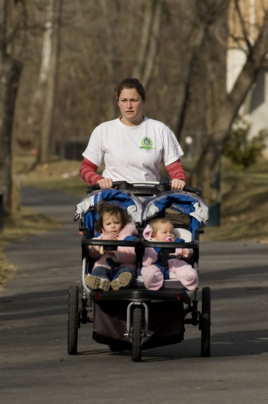 Rebekah Collins, of Front Royal, takes her daughters Sofia, left, 2, and Colette, 1, right, for a stroll along the Eastham Park Trail on a spring-like day Wednesday as temperatures hit the 50-degree mark.  Rich Cooley/Daily