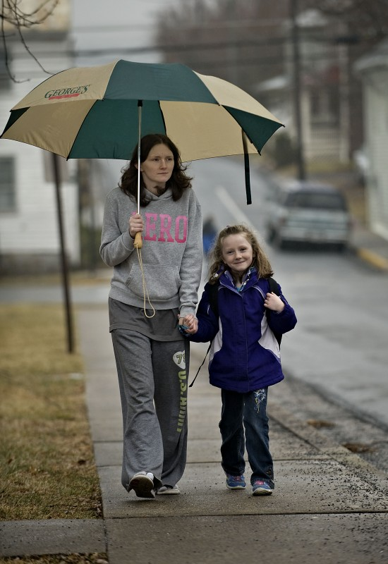 Angela Montgomery shares an umbrella with her daughter Skylar Edge, 6, as the pair walk  from the school bus stop at Main and Foundry Streets in Woodstock during a recent rainy afternoon. Temperatures are expected to drop today, with a high of 34 and low tonight near 13. The National Weather Service reports there is a 40 percent chance of snow showers today.   Rich Cooley/Daily
