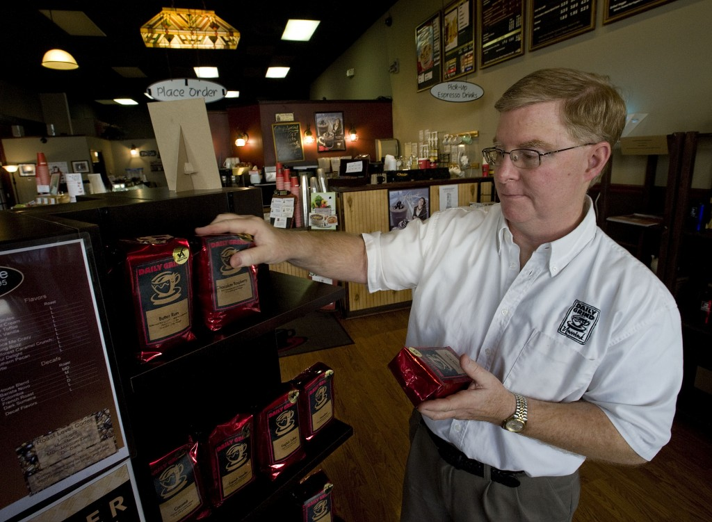 Herb Melrath, owner of the Daily Grind on Main Street in Front Royal, stocks his shelves with coffee last Thursday.   Rich Cooley/Daily