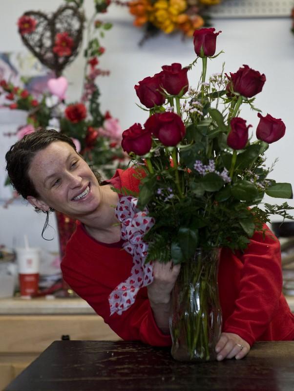 Lindsay Pfister arranges a dozen red roses for Valentine's Day inside her shop, Strasburg Florist, on West King Street in Strasburg on Thursday.  Rich Cooley/Daily