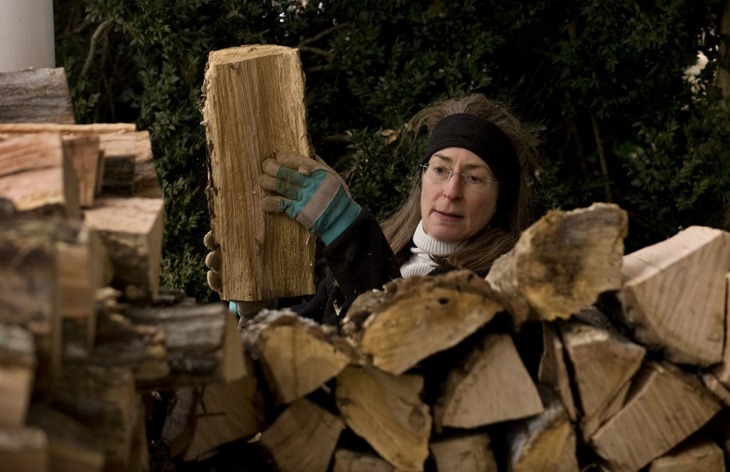 Kate Rudacille stacks firewood outside her Luray Avenue residence in Front Royal on a cold winter afternoon.  Rich Cooley/Daily