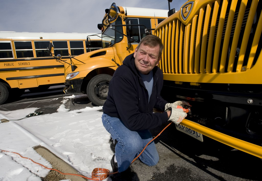 Shenandoah County school bus driver Ron Cromer plugs in an extension cord to power his engine block heater on this school bus outside Strasburg High School on Wednesday. Drivers were asked to come in and start their buses, which have been idle since last week, to prepare for the cold weather that is in the forecast for the next few days.  Rich Cooley/Daily