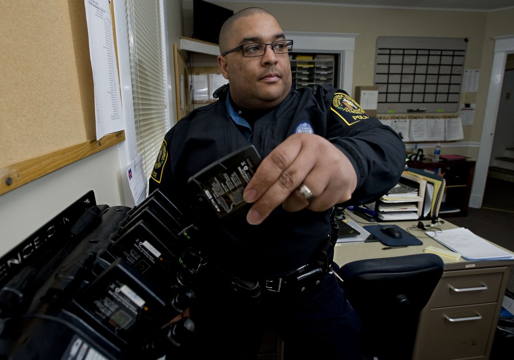 Woodstock Police senior officer Tyrone Fields pulls a battery out of a docking station for their body cameras and batteries. Body cameras have aided the department as a technology and evidence tool for officers.  Rich Cooley/Daily