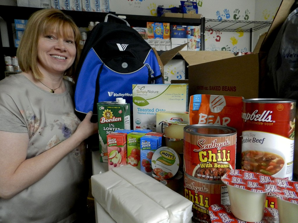 Lori Glascock holds a backpack used in the Warren County Backpack Program. During the school year, the program sends food home with hungry children to supplement meals over the weekend. During the summer, parents can pick up food each week at area distribution locations.  Josette Keelor/Daily