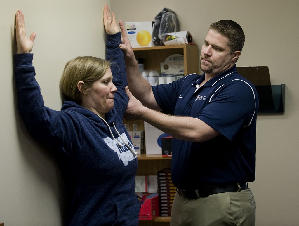 Dr. Jeremy Busch, a chiropractic and sports performance expert, shows his patient, Nicole Neely, 33, the wall angel exercise to reduce shoulder pain. Bush recently returned from the U.S. Olympics Training Center in California. Rich Cooley/Daily