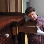Museum of the Shenandoah Valley  Curator of Collections Nick Powers examines a detail of a Winchester sideboard made by George Kreps in 1819. The sideboard will be included in a new exhibition just opened in the museum.   Photo by Rick Foster, courtesy of the MSV