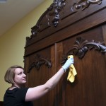 Museum of the Shenandoah Valley  Registrar and Collections Manager Kyle Bryner cleans a wardrobe on view in the newly opened exhibit.  The wardrobe was made in Winchester between 1855 and 1875 by German cabinetmaker John Andrew Vilwig [1822-1896]. Photo by Rick Foster, courtesy of the MSV.