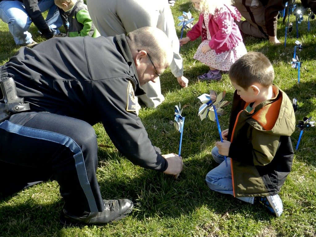 Woodstock Police Lt. Aaron Patti helps Carson Clark, 4, plant a pinwheel in front of the Shenandoah County Circuit Courthouse on Thursday morning. The pinwheel garden was planted to raise awareness for child abuse prevention.  Photo by Henry Culvyhouse