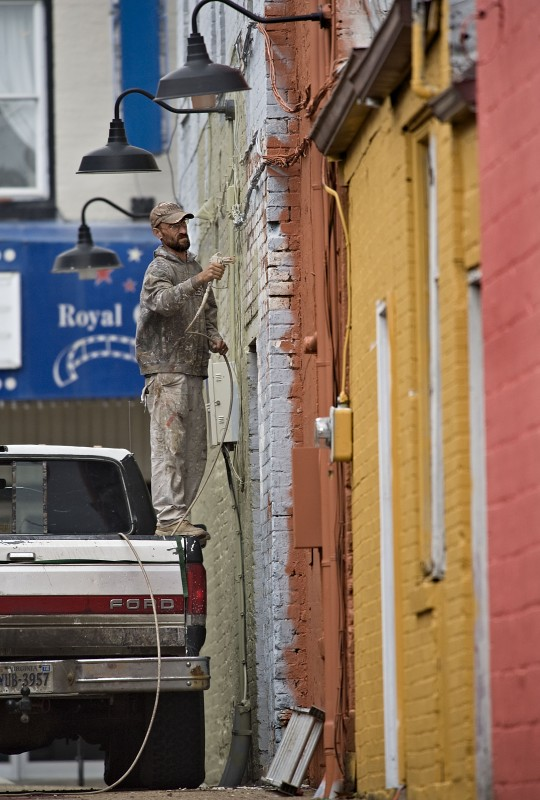 Jason Glascock, of Bentonville, uses the bed of his pickup truck to stand on as he spray paints this row of buildings along Kidd Lane off Main Street in Front Royal on a spring afternoon. Rich Cooley/Daily
