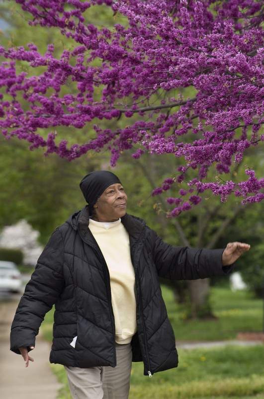 Barbara Sawyers, 63, of Front Royal, walks past a blooming redbud tree along Pine Street near her home recently. Rich Cooley/Daily