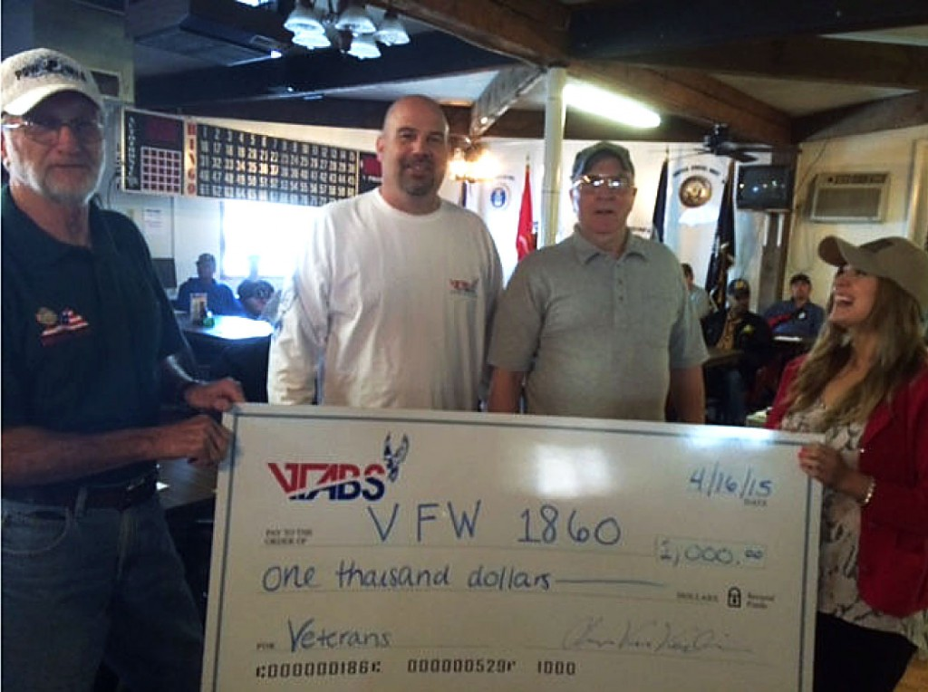 Lauren Gray, right, and Chris Van Voorhis, second from left, both of V-Tabs, present a donation of $1,000 to the Veterans of Foreign Wars Post 1860. Accepting the check are post Quartermaster Scott Simmons,  left,  and post member Tom Sayers, second from right.  Courtesy photo