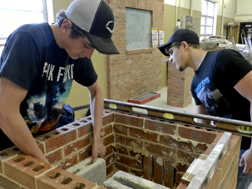 Triplett Tech masonry students Zach Hutchison, 19, left,  and Jeremy Morris, 18, work on a chimney in the shop at the school in Mount Jackson on Wednesday. Morris won first place in masonry at the SkillsUSA state State Leadership Conference & Skills Championships held April 17-18 in Roanoke, and Hutchison won first place in brick laying.  Josette Keelor/Daily