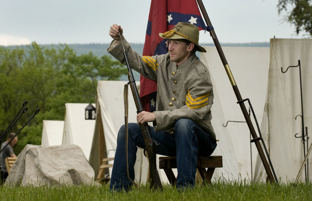Zane Smith, 34, of Baltimore, a member of the 18th Virginia Calvary, checks his Civil War Enfield rifle outside his tent at New Market Battlefield Park during last year's event.  The annual New Market Battle Reenactment is this  weekend. Rich Cooley/Daily file photo