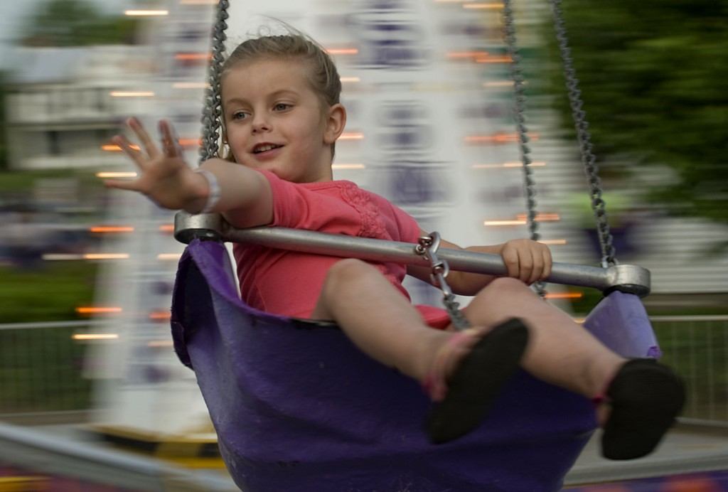 Kiera Miller, 5, of Strasburg rides the swings during the Mayfest Carnival on Friday evening on the Strasburg Town Lot.  Mayfest continues today through Sunday with the parade, which begins at 3 p.m., highlighting Saturday's activities.  Rich Cooley/Daily