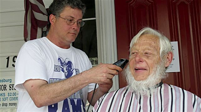Strasburg town Councilman Bob Baker has his beard shorn by Gents Barbershop owner Marvin Hill after Baker promised to shave if the Strasburg Community Library could raise an additional $1,000 for its capital campaign. Hill did the shave for free.  The fund drive started last November and raised about $27,500. Courtesy photo