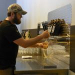 Bartender James Montgomery pours a beer during the grand opening of the Escutcheon Brewing Company, at 142 W. Commercial St. in Winchester. Hilary Legge/Daily