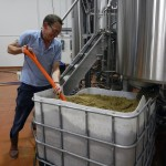 John Hovermale, head brewer of new Escutcheon Brewing Company in Winchester, shovels out the leftover grain from a recent batch of beer. This spent grain is given to a local farm where it is used as feed for the animals. Hilary Legge/Daily