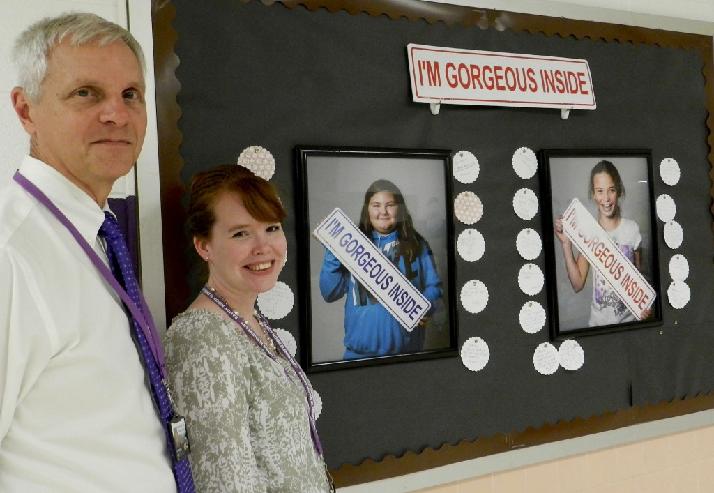 """Herbert Wilburn, left, National Board Certified library media specialist at Sandy Hook Elementary School in Strasburg, and Christine Jones, a school instructional coach, stand beside a bulletin board in the hall recognizing Sidney Duckworth, pictured left, and Kiersten Wilson among 49 students chosen for the school's """"I'm Gorgeous Inside"""" project, which started last November. Both 11-year-old fifth graders are from Strasburg.  Josette Keelor/Daily"""