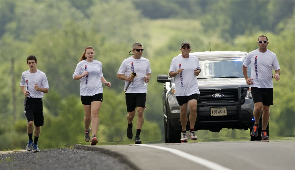 Runners hit the pavement along Route 11 north of Strasburg on Tuesday morning during the Special Olympics Law Enforcement Torch Run. Shown running are, from left, Matt Chimento and Holly Funkhouser, both members of the Strasburg High School track team, and Strasburg Police Department officers Wayne Sager, Mike Chimento and Scott Thompson. Winchester City and Frederick County officers started on the Loudoun Street Mall in Winchester and ran south to the Shenandoah and Frederick County line at Cedar Creek. Runners from Strasburg carried the torch from the county line to the Old Mill Grill Restaurant in town. Wednesday's leg will start in Woodstock and go to New Market.  The eight-day torch run involves more than 2,000 law enforcement officers and personnel representing more than 200 law enforcement agencies across Virginia and will end in Richmond. Rich Cooley/Daily