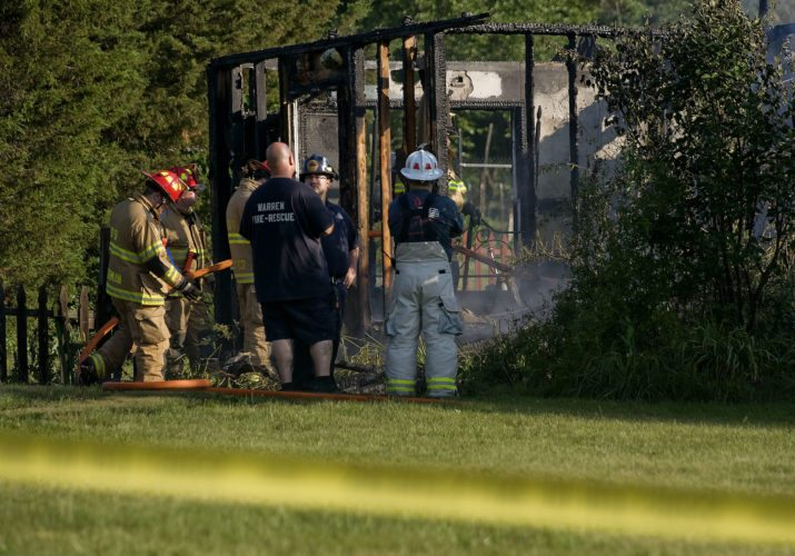 Firefighters and investigators stand outside this burned-out section of a home at 30 Cedar Lake Court in Warren County on Sunday morning. A man's body was found while firefighters were battling the blaze.  Rich Cooley/Daily