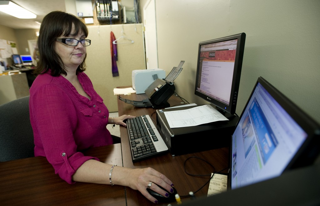 Melissa Brewster works on her computer inside the Warren County Department of Social Services in Front Royal. Brewster was a prior recipient of benefits through the agency and was a volunteer before landing a job with the agency.   Rich Cooley/Daily