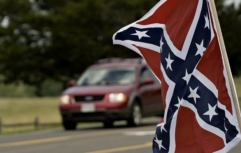 A Confederate flag flies outside Cedar Creek Mercantile in Middletown as a car passes along Valley Pike on June 23.    Rich Cooley/Daily