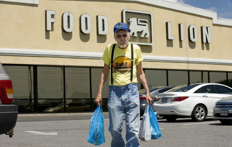 Richard Radi, of Middletown, walks outside the Strasburg Food Lion with grocery bags Wednesday afternoon. The parent companies of Food Lion and Martin's are merging to create a $29 billion grocer, putting it into a position to compete with Wal-Mart and other stores.   The merger is expected to be finalized next year. Rich Cooley/Daily