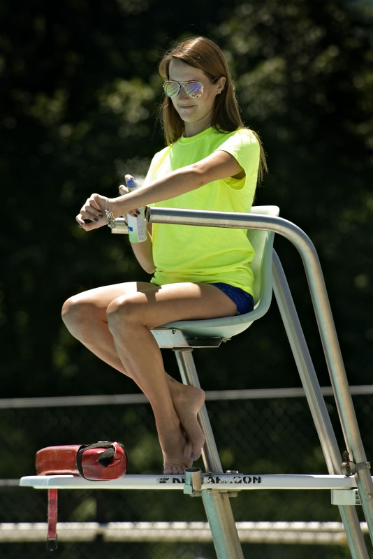 Kathleen Maynard, 22, of Woodstock, applies sunscreen while keeping watch as a lifeguard at the  W.O. Riley Park in Woodstock recently. Rich Cooley/Daily