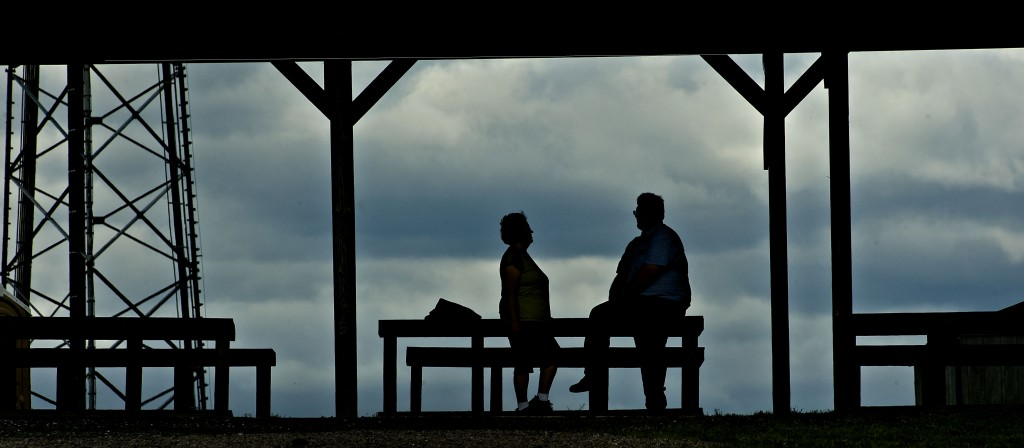 Chris and Terry Richards are captured in silhouette under the shelter at the Shenandoah Valley Flea Market north of New Market recently.  Rich Cooley/Daily