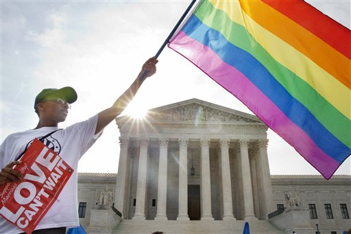 Carlos McKnigh,t of Washington, waves a flag in support of gay marriage outside of the Supreme Court on Friday. AP