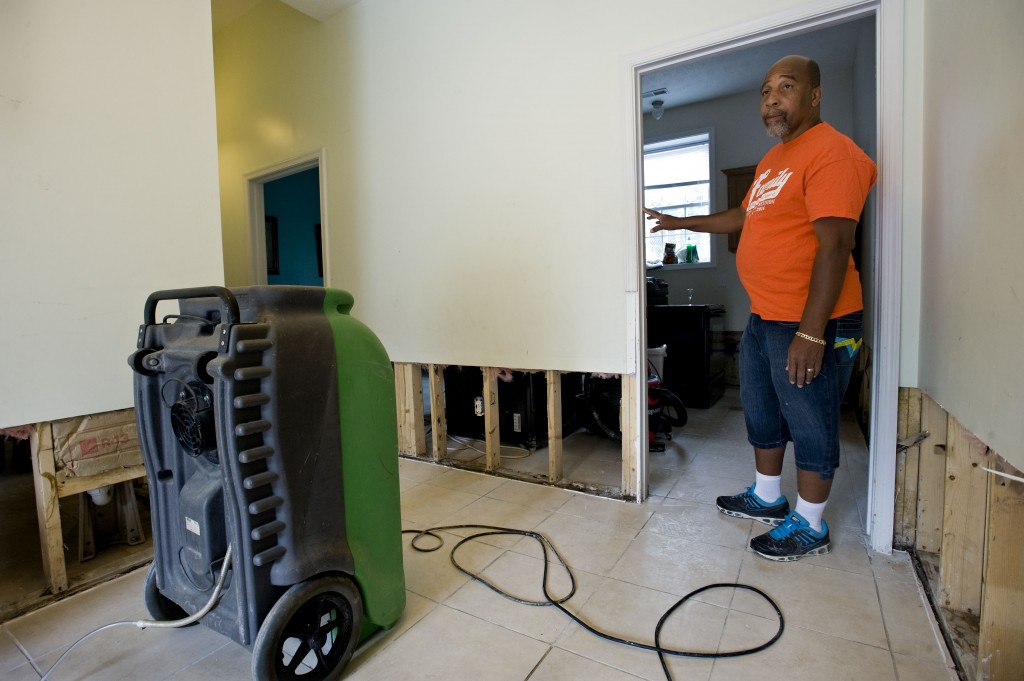 Leon McCray, pastor of Lighthouse Church and Marketplace Ministries, stands inside the foyer of his church in Woodstock while a dehumidifier dries out flood damage Wednesday afternoon. Rich Cooley/Daily